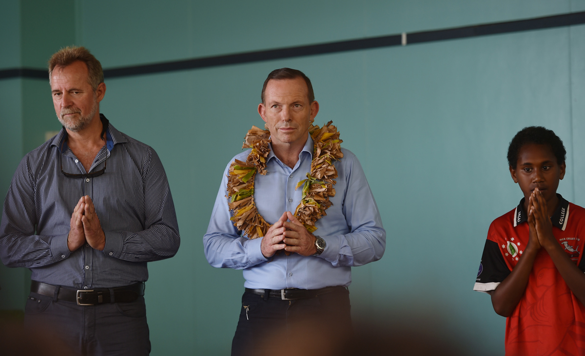 Prime Minister Tony Abbott (centre) with Indigenous Affairs minister Nigel Scullion and a child pray during a visit to Mer Eruer Uteb Tagai State College on Mer Island in the Torres Strait, Australia. © Tracey Nearmy AAP