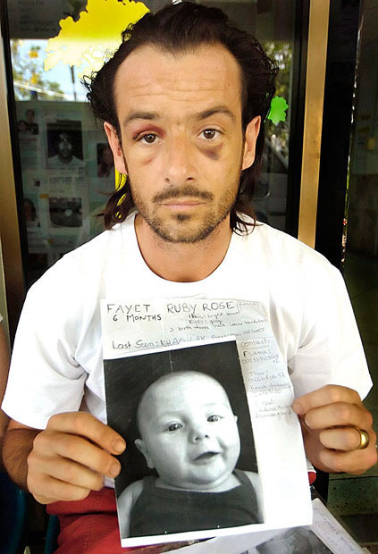 Patrice Fayet holds a photo of his 6 month old baby daughter Ruby Rose at Phuket Hospital. She was washed from his grasp and never seen again.Pic ©  Brian Cassey