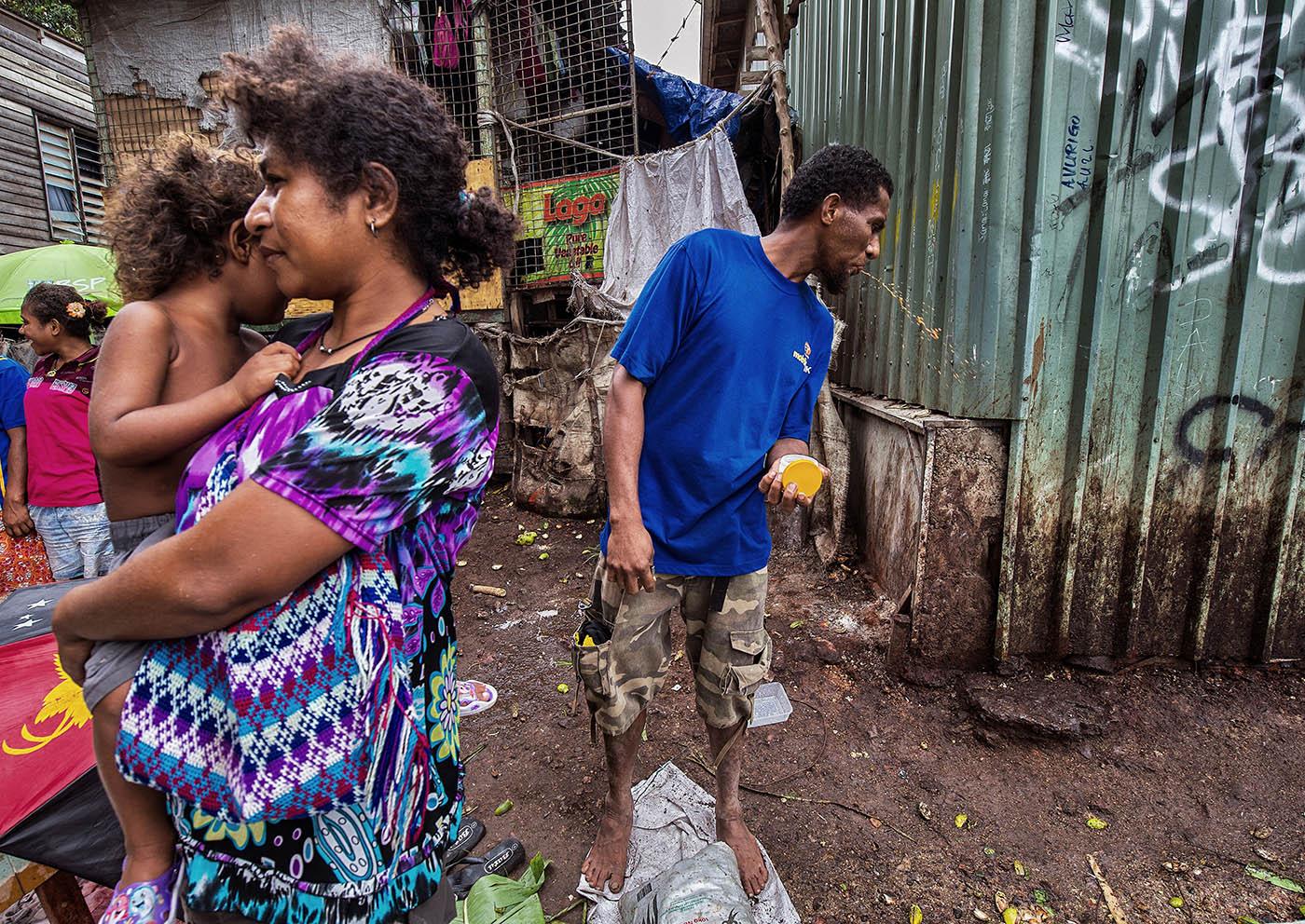 A man spits betel nut (buai) at Hanuabada market.  © Brian Cassey