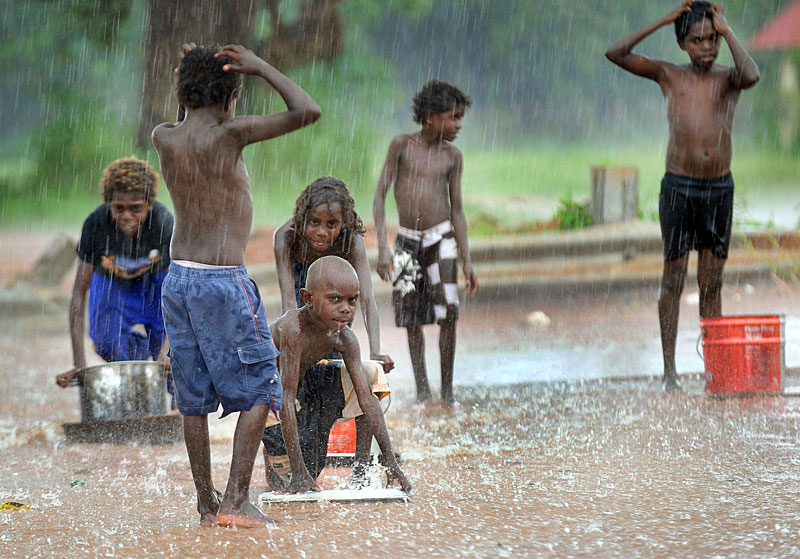 Truant Aurukun children improvise boat play during a tropical downpour ... while their school stands nearly empty close by.© 2008 Brian Cassey