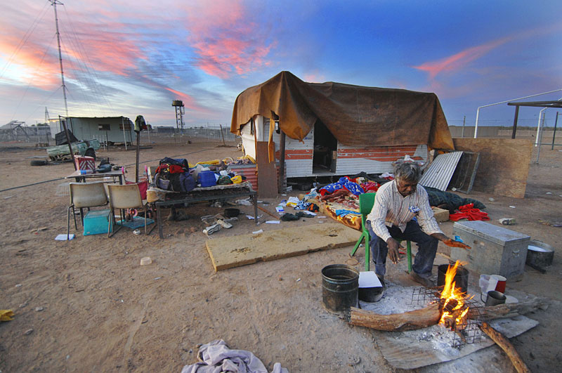 Mark Webb tries to get warm at dawn while his seven children sleep in the open on a fraying mattress outside his wrecked van. Urandangi has no power, no water and no sanitation. © 2008 Brian Cassey