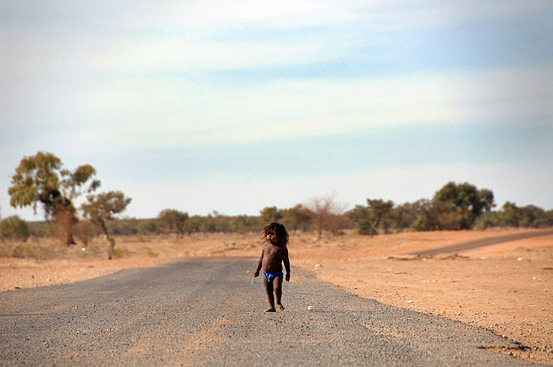 A lone child wanders the main road into Urandangi, Western Queensland. The community has no power, water or sanitation. © 2008 Brian Cassey