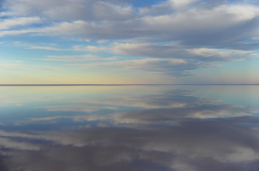 Subtle pastel tones and clouds are reflected in the waters filling Lake Eyre at sunset.© Dean Lewins/AAP Image 2010