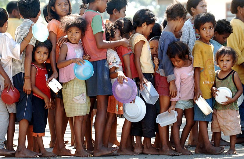 Children forced to take shelter at an IDP camp, line up for a bowl of porridge in the capital Dili.© 2006 Dean Lewins/AAPImage