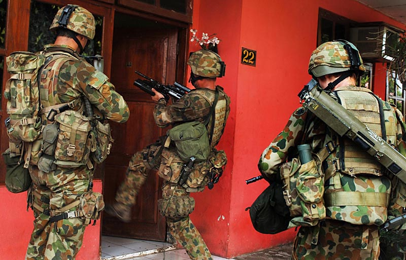 Australian troops kick in the front door of a home in the Becora district of the capital Dili as they conduct house to house searches.© 2006 Dean Lewins/AAPImage