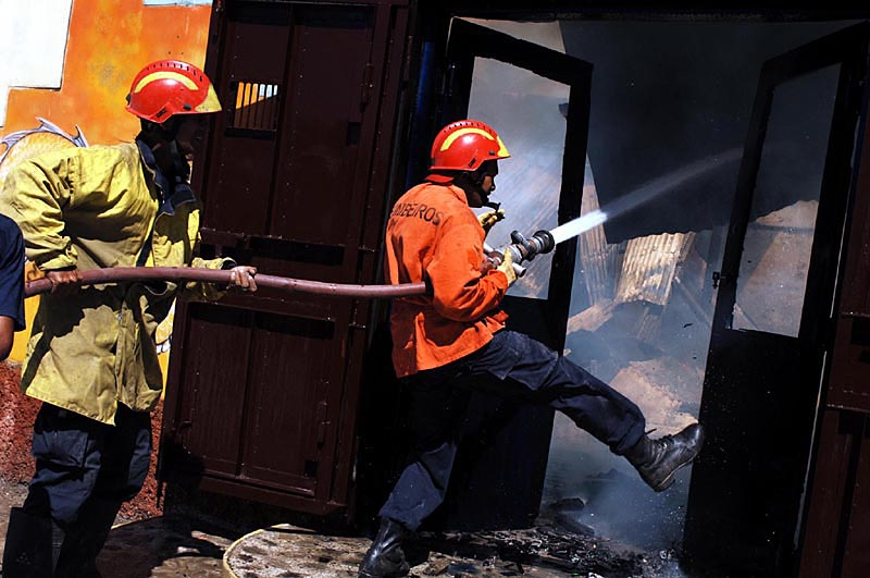 Local fire fighters extinguish a shop fire after an arsen attack in the capital Dili.© 2006 Dean Lewins/AAPImage