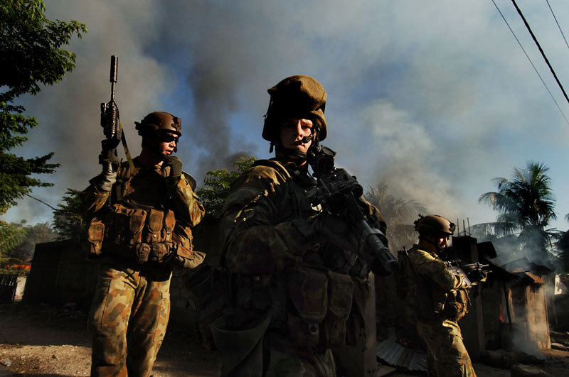 Australian commando soldiers secure a safe passage as they extracate women and children out of a suburb in the capital Dili.© 2006 Dean Lewins/AAPImage