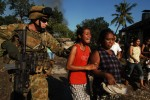 Australian commando soldiers escort distressed women and children out of a suburb in the capital Dili.© 2006 Dean Lewins/AAPImage