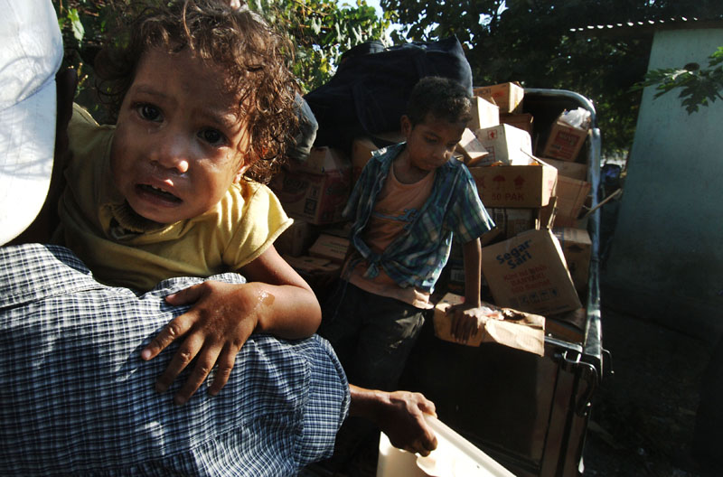 An East Timorese family pack up their belongings after continued arson attacks in the Comoro district in the capital Dili.© 2006 Dean Lewins/AAPImage