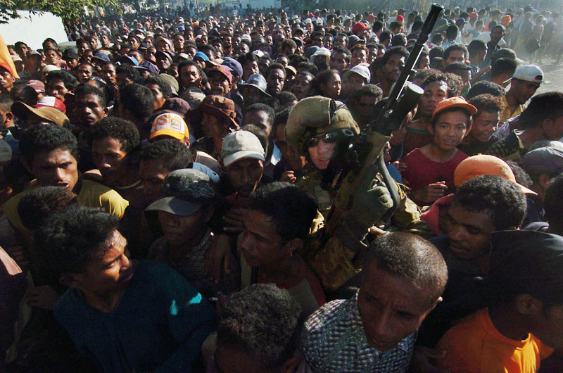 An Australian soldier tries to push through the huge crowd after hungry East Timorese broke into the rice storage facility causing chaos in the capital Dili.© 2006 Dean Lewins/AAPImage