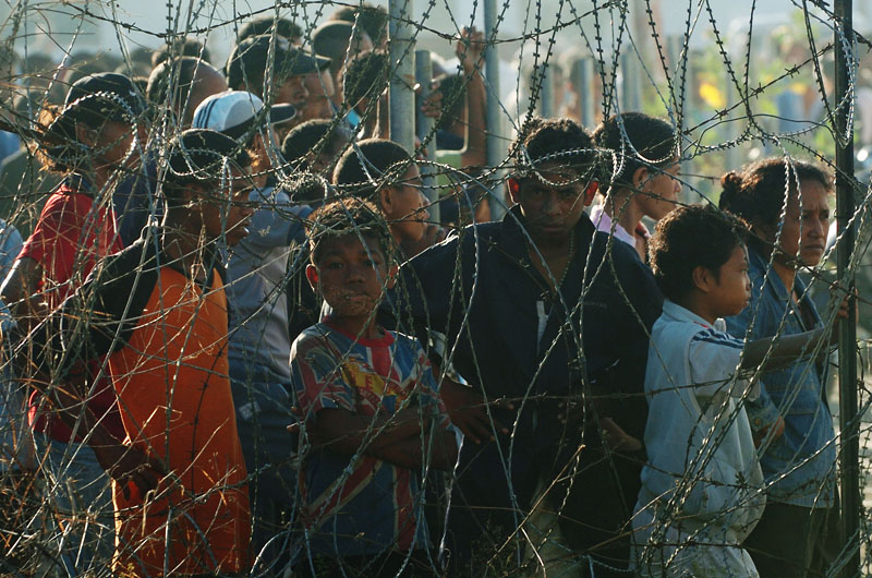 Some of the tens of thousands of starving East Timorese wait behind razor-wire at a rice distribution depot in the capital Dili© 2006 Dean Lewins/AAPImage