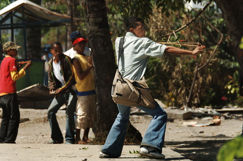 A youth draws back his sling shot as Easteners and Westeners continue their running battle around the Comoro market in the capital Dili.© 2006 Dean Lewins/AAPImage