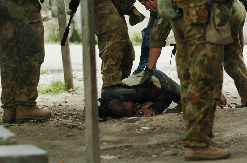Australian special forces troops detain disarm a man during an operation in one of the major trouble spots in the capital Dili.© 2006 Dean Lewins/AAPImage