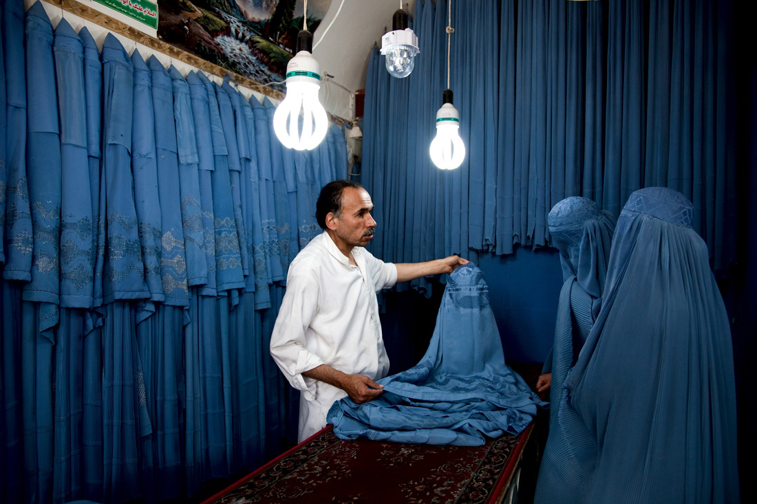 © GRAHAM CROUCH - 14.05.2012 Two burqua clad women shop at a locally owned garment shop in Herat Afghanistan.