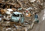 A man walks past the damage in the Northern Coastal town of Ofunato were destroyed after a 9.0 earthquake caused a tsunami which hit the eastern coast of Japan on the 11th March, 2011.