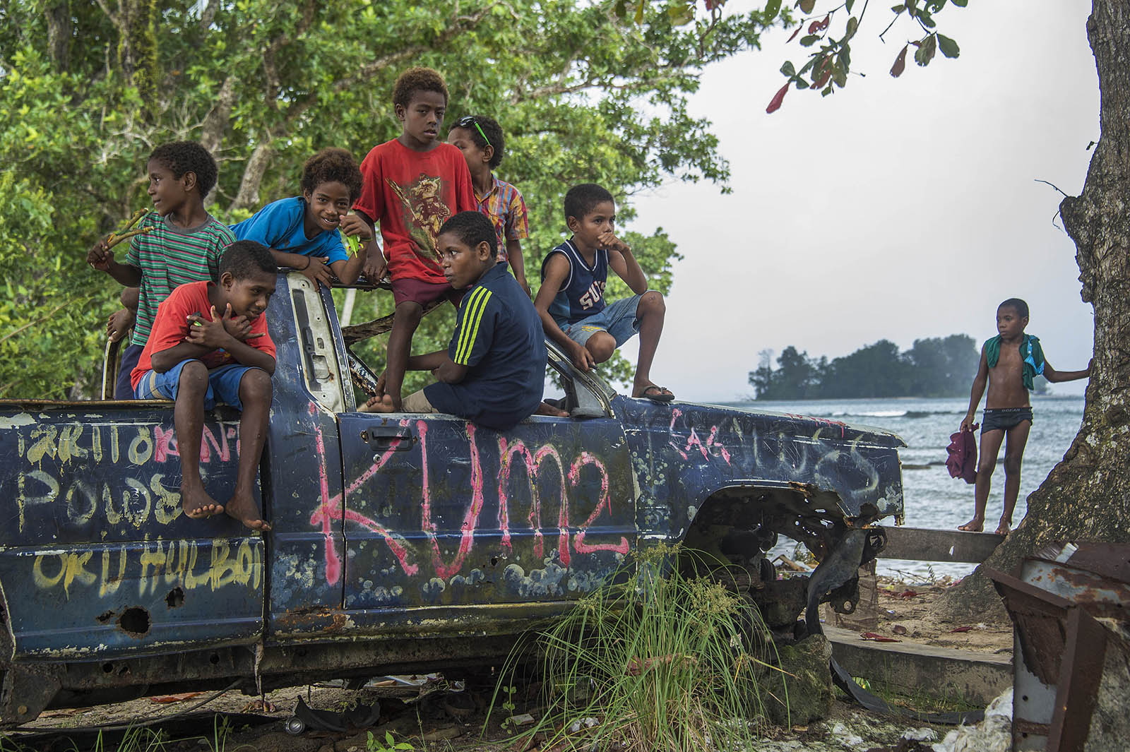 Children play on an abondoned car at the beach near Lorengau, Manus Island PNG. © Brian Cassey