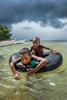 Storm clouds gather over Manus Island as children enjoy the warm clear tropical waters.© Brian Cassey