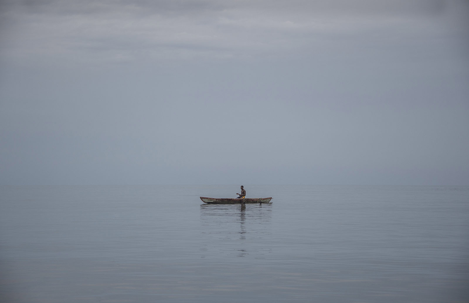 A Manus islander on his outrigger canoe in a sea of tranquility and calm just out from the Manus Island capitol Lorengau. © Brian Cassey