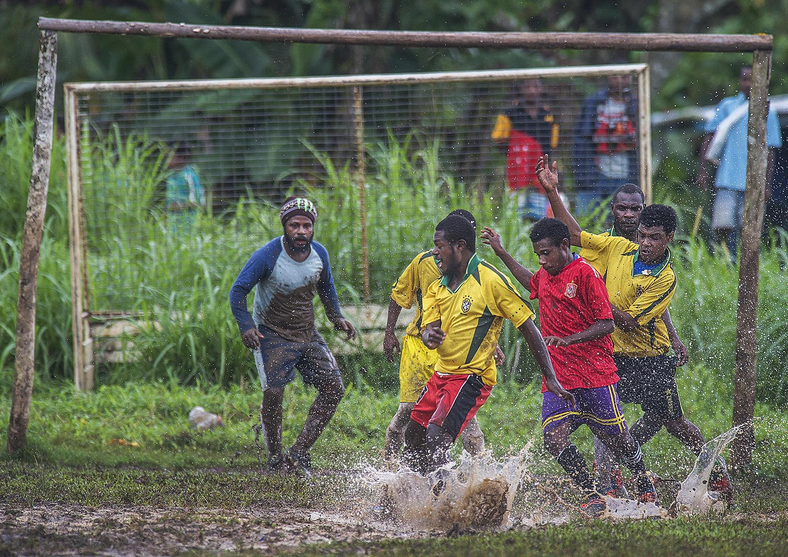 Two local teams battle the elements and each other during a football (soccer) game in Lorengau  - the capitol of Manus Island PNG. © Brian Cassey