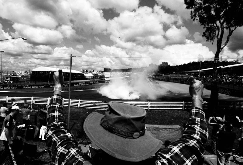 A fan gives a thumbs up in appreciation of a half time entertainment ute burnout at an area of the Bathurst track known as {quote}hells corner{quote}. Mt Panorama, Bathurst, NSW, Australia.  © Sam Mooy 2008