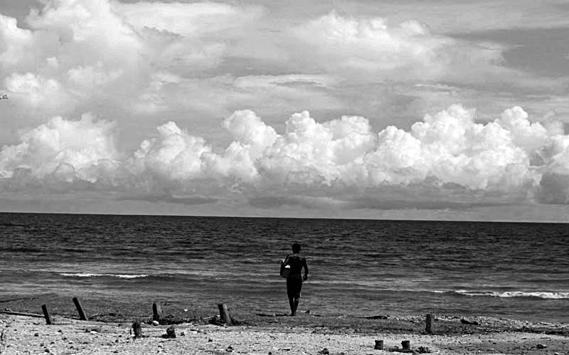 A man looks out to sea worried that another wave is coming.© Sam Mooy 2007 for The Australian