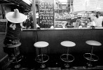 A man wearing a sombraro hat sits patiently for his coffee in Adelaide's central markets. © Sam Mooy 2008