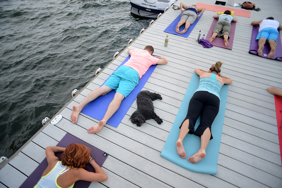 Okanagan Lake residents practice yoga on a pier over the lake.