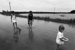 A young family take to the shallow floodwaters near the town of Brushgrove, New South Wales. © Sam Mooy 2011