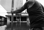 Local shop owners wait for floodwaters to recede in the township of Lawrence, New South Wales. © Sam Mooy 2011