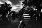 Local resident surveys the damage of floodwater through his caravan park, in the town of Boggabilla, New South Wales. © Sam Mooy 2011