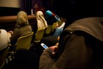 Asmaa texts her friend while waiting for a performer to take the stage during an Islamic poetry night.