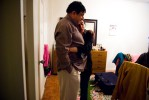 Ambreen hugs her dad while he packs his suitcase.  Ambreen's father works in India and only sees his wife and two children twice a year.