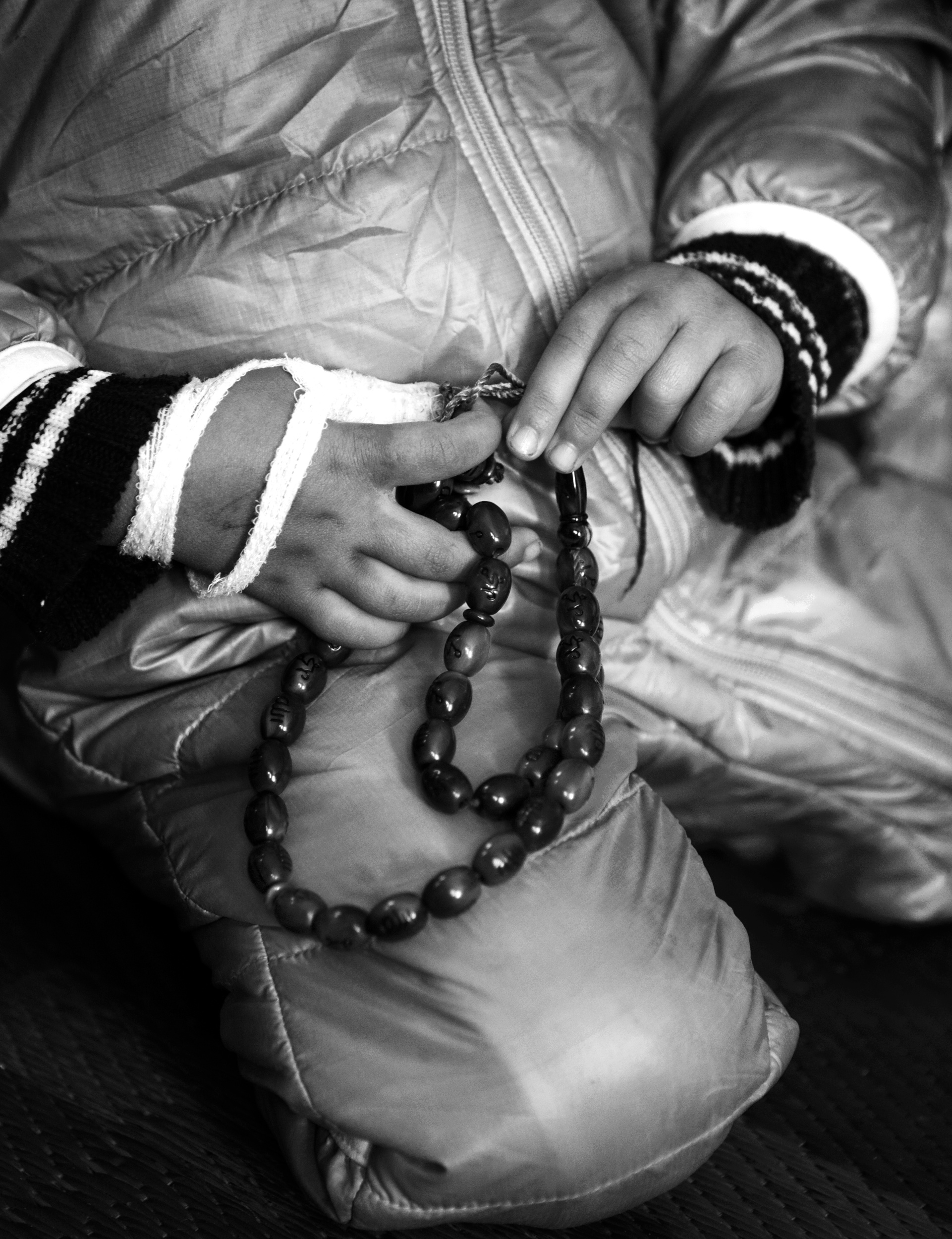 Salwa plays with her father's prayer beads.