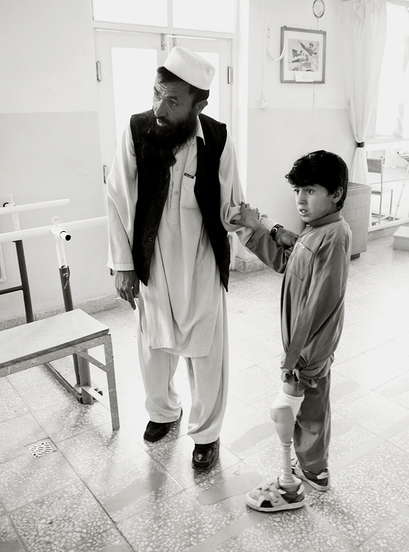 Ataqullah with his father at the ICRC limb-fitting centre in Kabul. A year before, while walking to school, Ataqullah stepped on a landmine losing an arm and a leg.