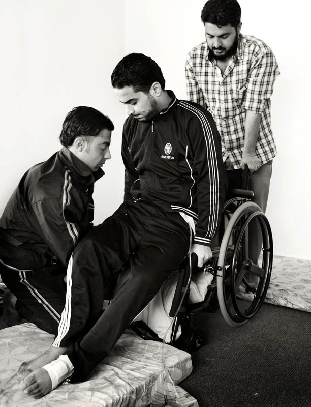Shaher is helped into his wheelchair by his two brothers.