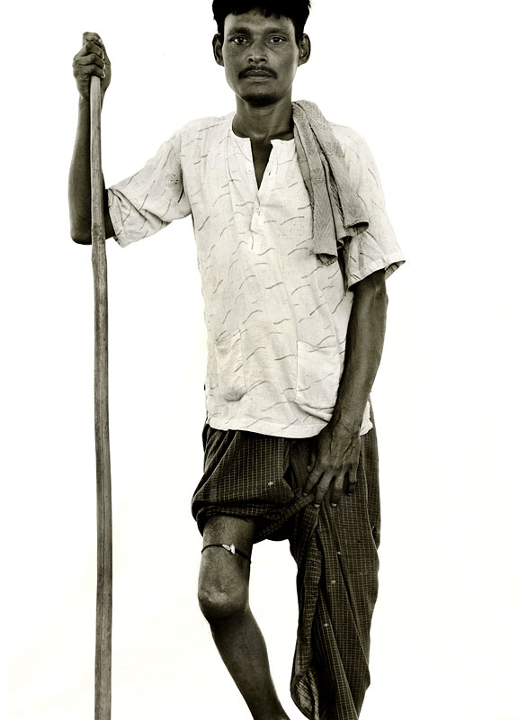 Kamal Hussein, 30.Crippled leg.His gnarled walking staff lends Kamal a wizardly aspect that belies his having seen barely three decades. He explains with unexpected good cheer how the shattered leg that drags uselessly in the dust behind him was incyrred in a beating from the Nasaka, who he says came across him collecting bamboo in the jungle and decided to punish him without explanation. He says that making his way around the camp is extremely difficult, but that life here is a {quote}paradise{quote} compared to Burma - largely the result of a new found freedom to pray at a handful of improvised mosques. {quote}In Burma our faith was something forwhich we were made to feel ashamed,{quote} he says, {quote}but here we are all Muslims, and being able to call upon Allah five times daily gives me the strength to endure any suffereing.{quote}