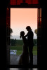A couple is silhouetted in a doorway during sunset as they hold each other gazing at each other.