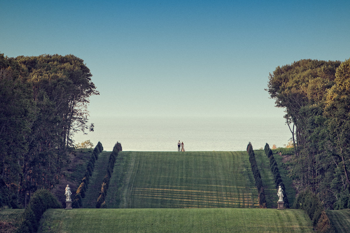A huge landscape view from the back lawn of the Crane Estate. A bride and groom hold hands after walking far down on the great lawn overlooking Crane Beach on  beautiful summer day with blue sky.