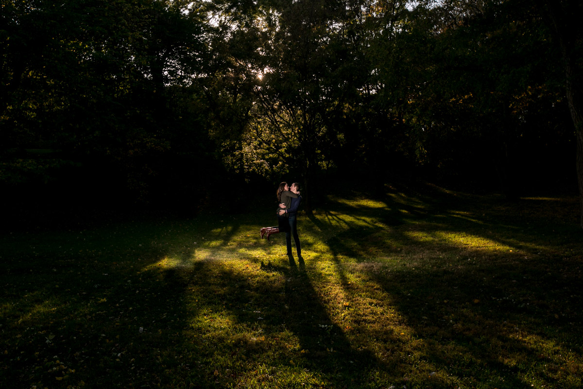 Sunlight through trees on a man holding a women woods.