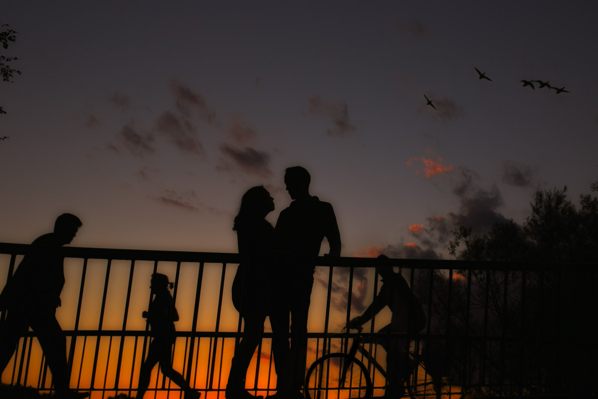 Silhouetted couple on bridge at sunset.