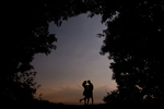 A beautiful sunet and silhoutted trees make backdrop for couples passionate kiss in the woods or forest.