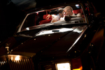 A couple in a Rolls Royce have a romantic moment as they look into each others eyes at night with dramatic light.