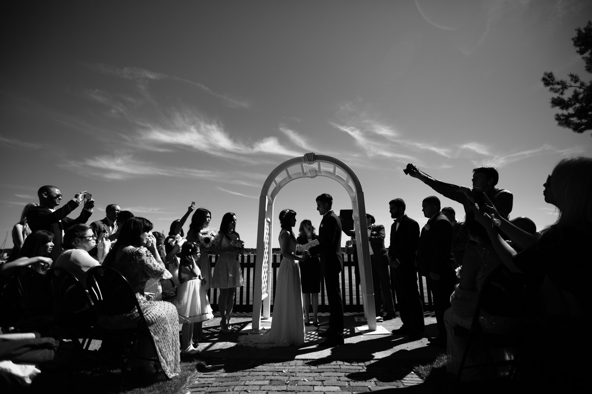 A wedding ceremony with dark shadows and strong sunshine during a Summer outdoor wedding.