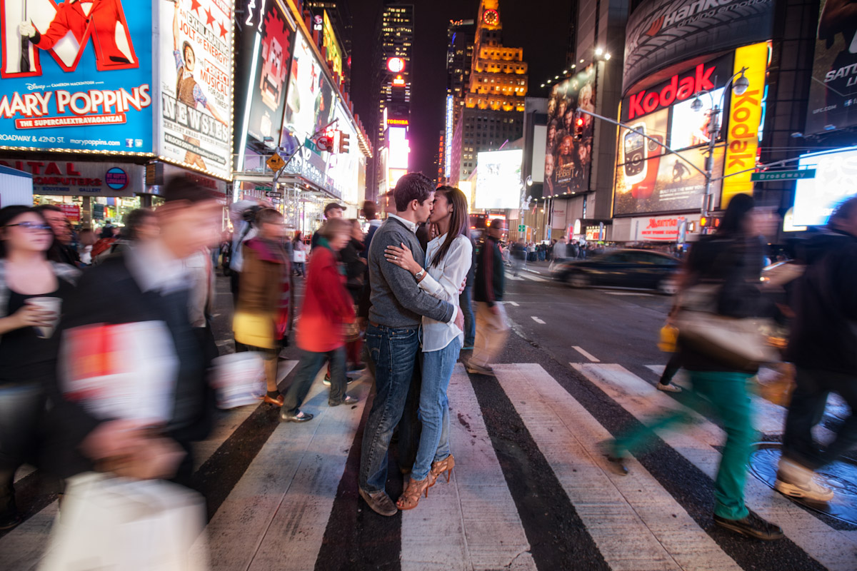 A couple share a passionate kiss in a crosswalk at a city at night as people and cars rush by them in a blurr.
