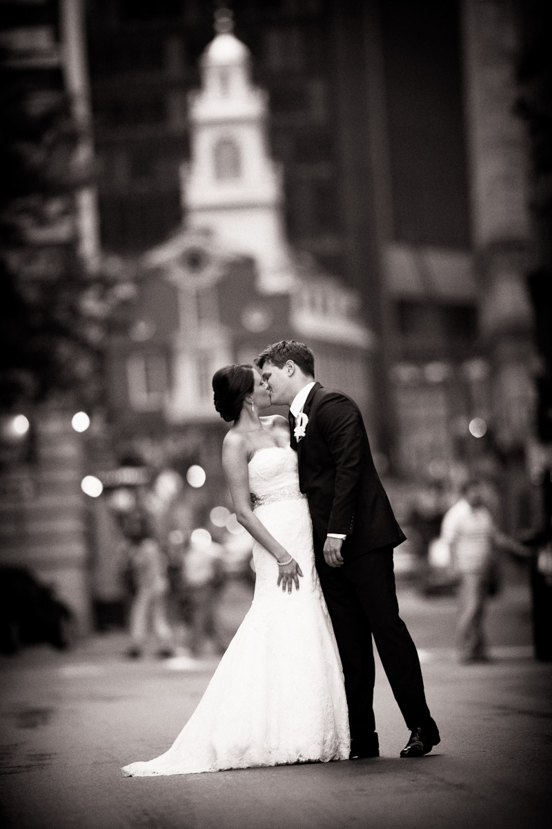 A  black and white photo showing a groom giving his bride a passionate kiss in the street in front of the Old State House.