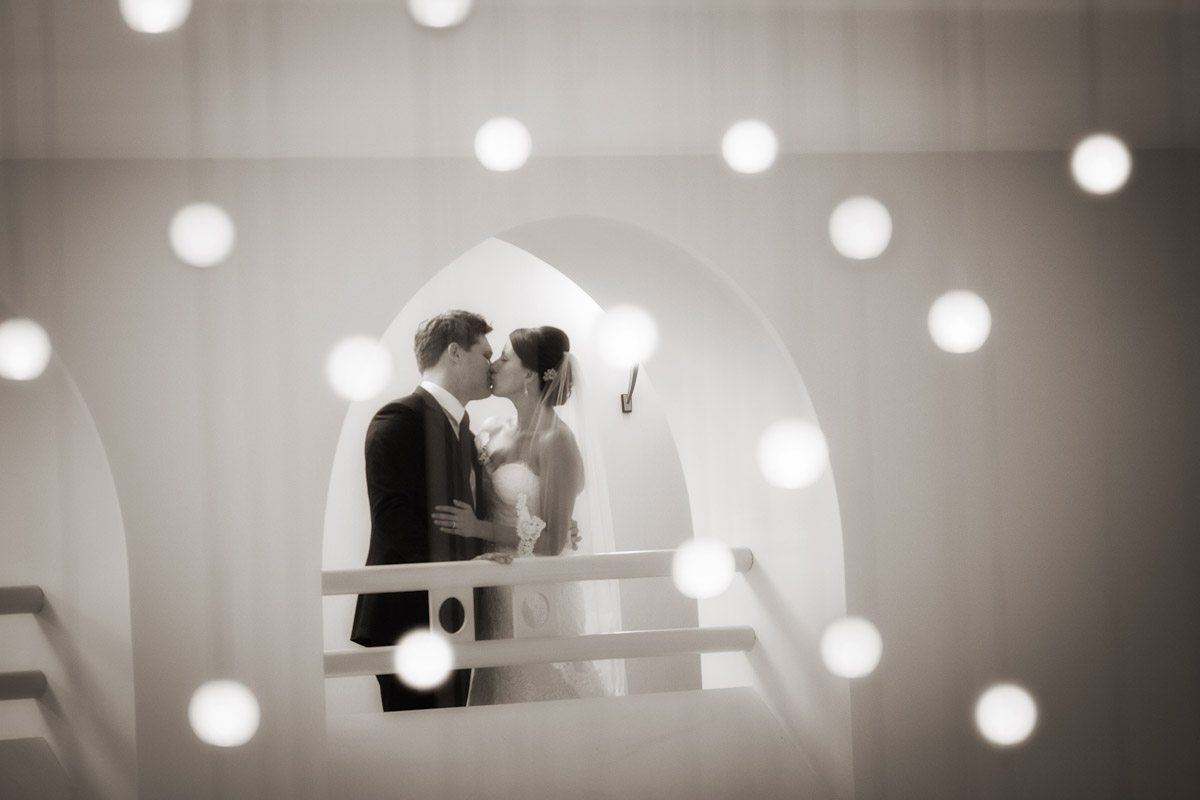 A bride and groom embrace in an alcove with hanging lights dangling in front of them.