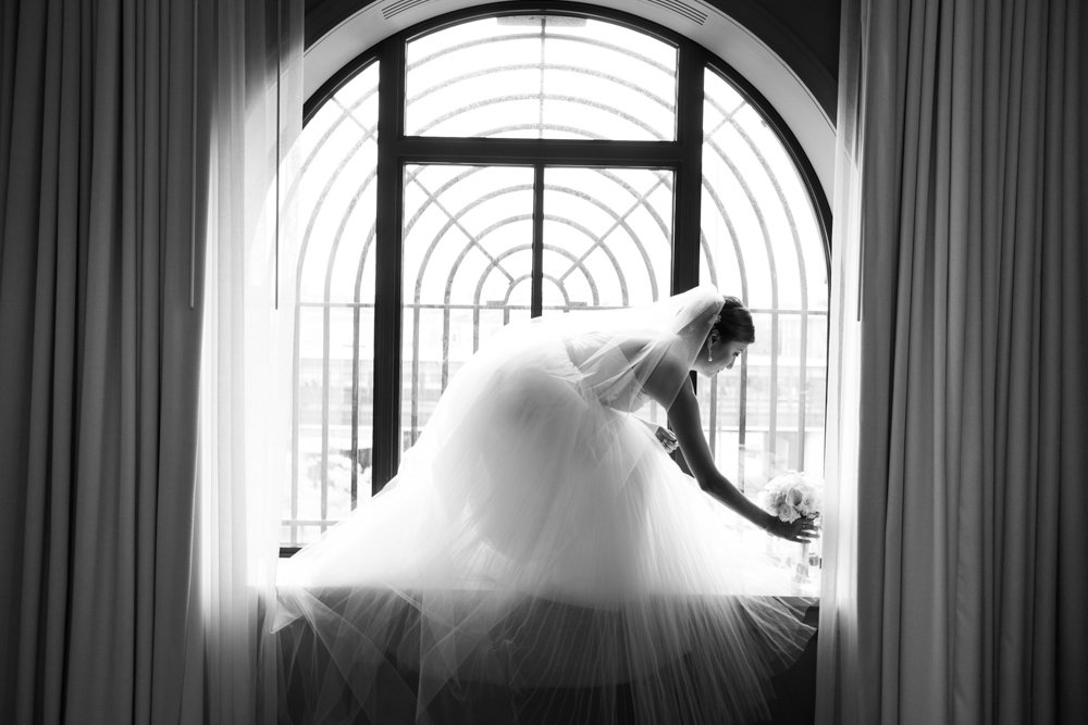 Black and white photo of a bride framed with beautiful window and natural light admiring her bouquet.