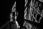 Black and white photo, bride and groom kiss  in a stairwell with very contrasty light from sunshine through a beautiful window in natural light