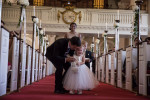 A flower girl walking on a red carpet is comforted by her father as she cries walking down aisle at Memorial Church in Harvard University