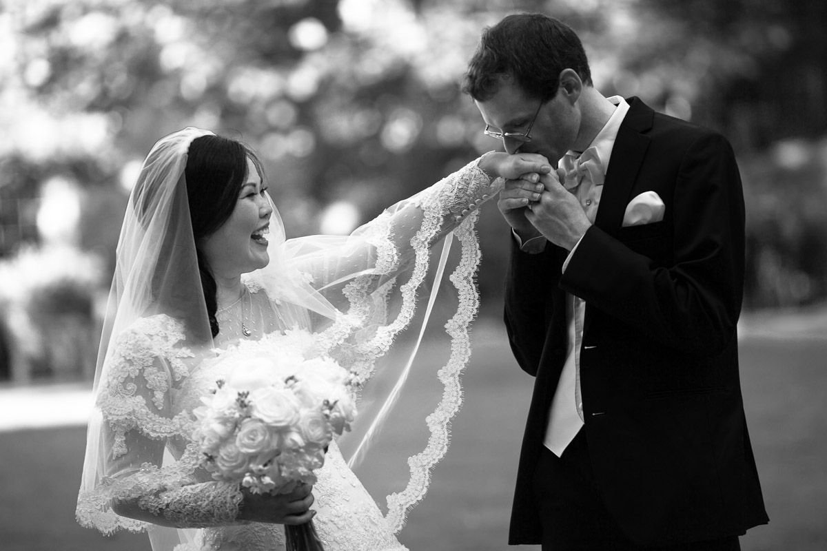 A groom kisses his aisan bride on her hand outside on a beautiful day.